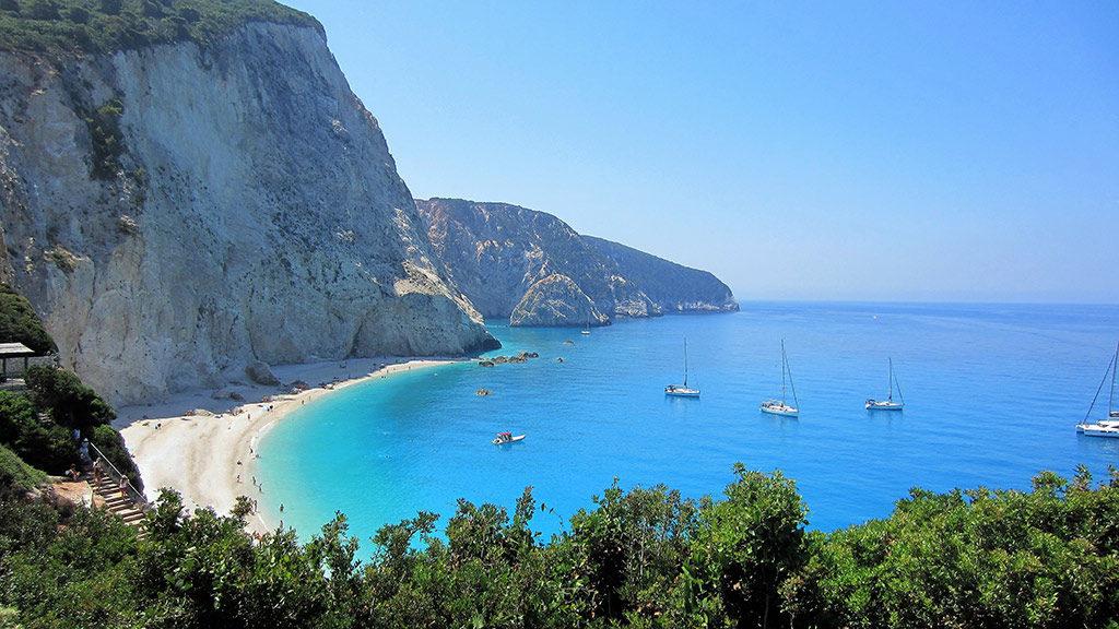 Blick auf Bucht von Porto Katsiki mit hohen Kalksteinfelsen auf Lefkada, weißer Strand, türkisblaues Wasser, Boote ankern im Wasser