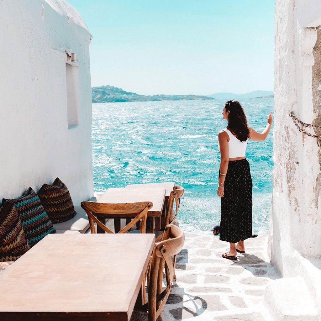 Frau steht an weißer Hauswand und blickt auf das Meer