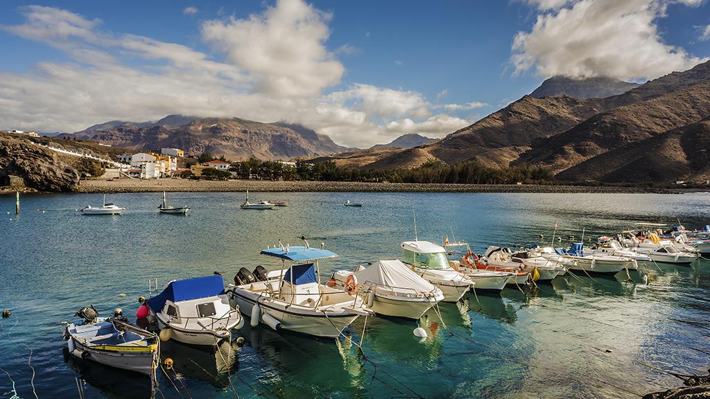 Kleine Boote ankern im Hafen von La Aldea de San Nicolas, im Hintergrund Berge