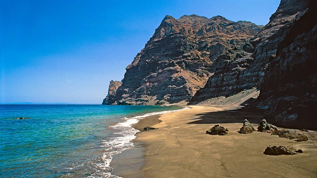 Blick auf Bucht von Güi Güi mit kleinem Sandstrand und hoher Felsküste