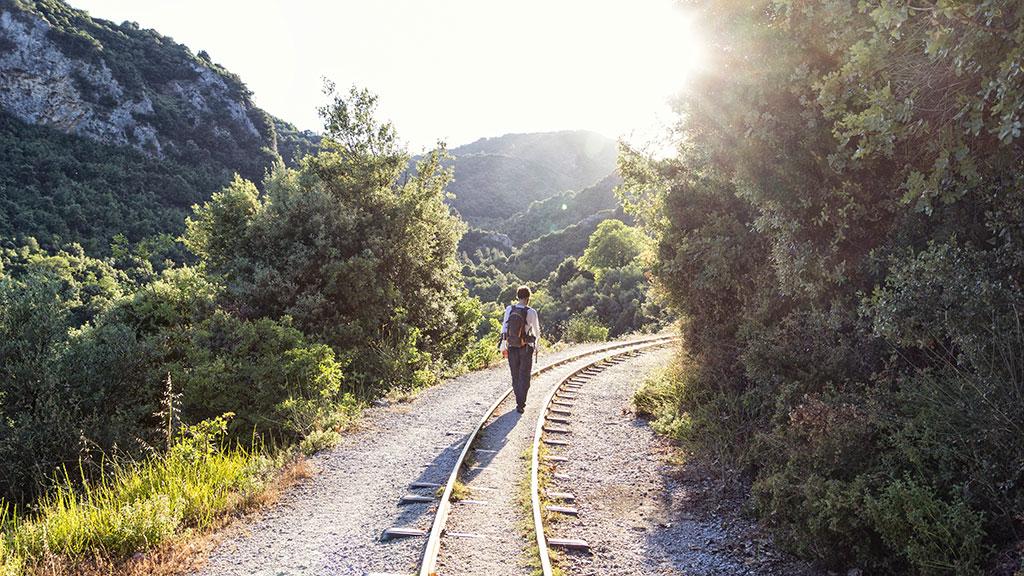 Mann wandert auf stillgelegten Bahnschienen im grünen Gebirge, Pilion