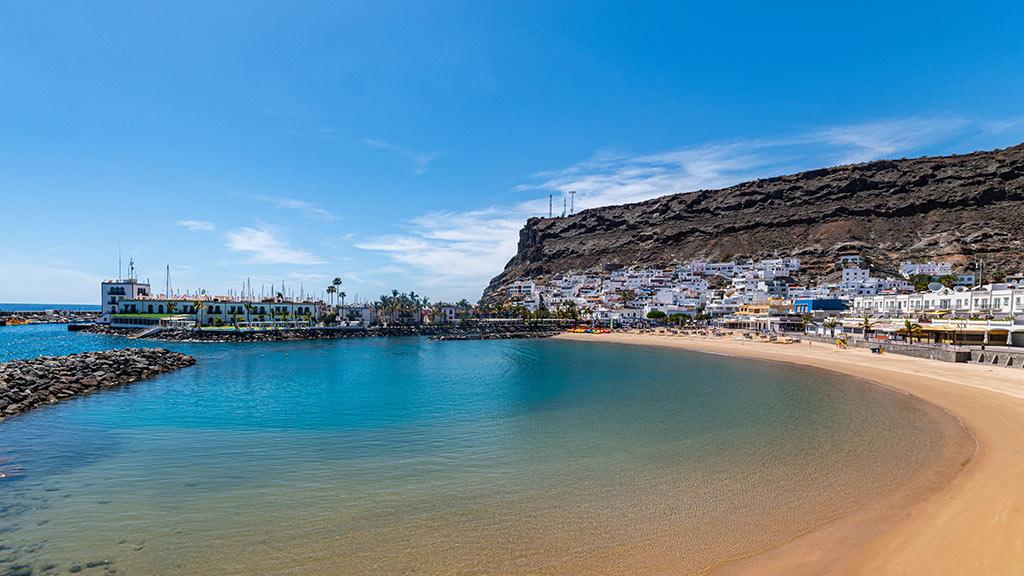 Blick auf Bucht von Puerto de Mogan mit Strand und Häusern im Hintergrund