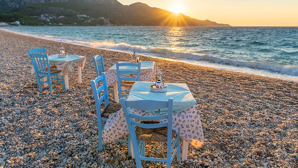 Zwei Tische mit Stühlen stehen am Kiesstrand von Kokkari, Abendstimmung
