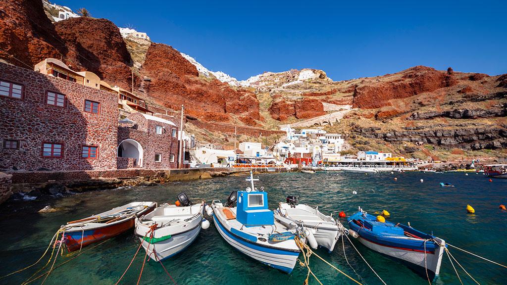 Blick auf Hafen von Ammoudi auf Santorin, rote Felsen, Fischerboote