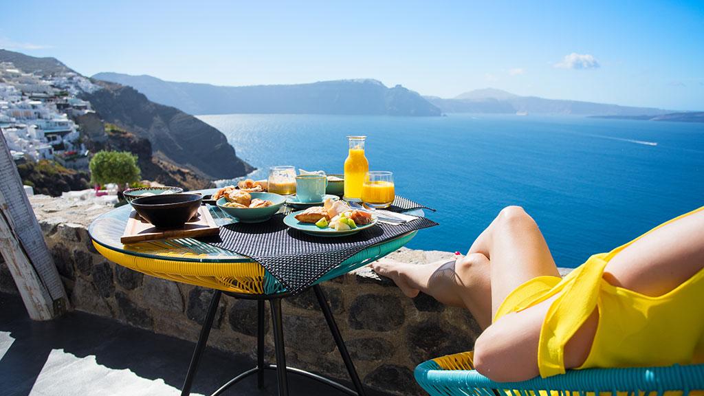 Frau in gelben Badeanzug genießt Frühstück auf Balkon mit Blick auf Oia in Santorin