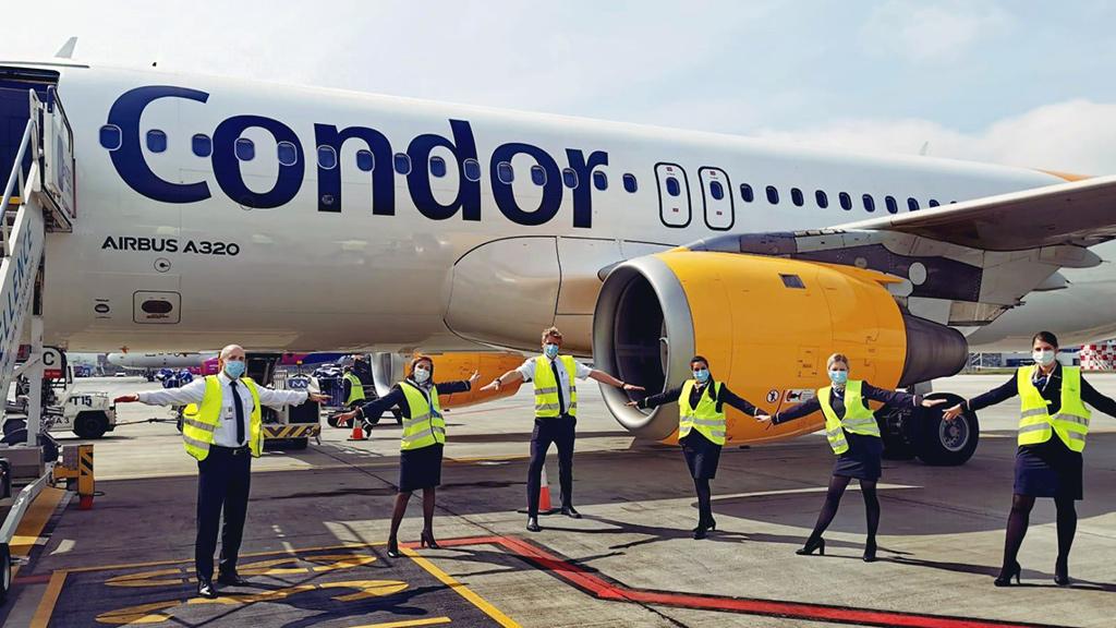 Condor Crew in gelben Warnwesten steht vor Condor Flugzeug