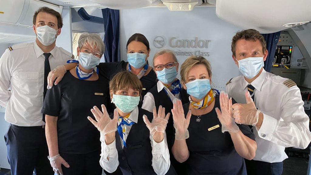 Condor Crew mit Mundschutz in Flugzeugkabine