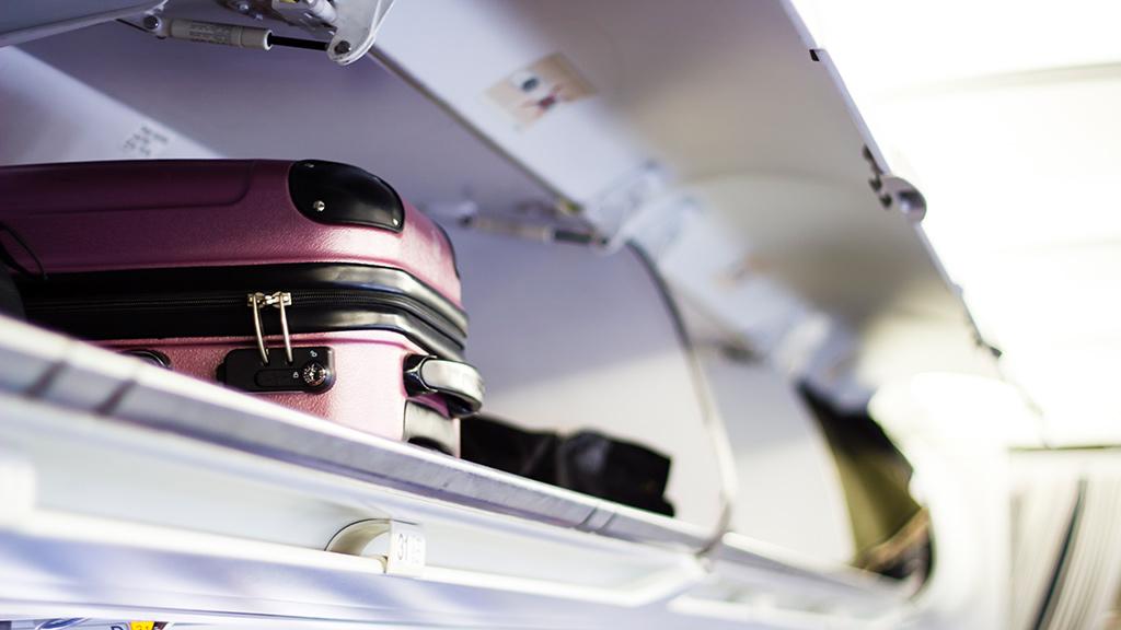 Handgepäck liegt in Gepäckfach in Flugzeugkabine