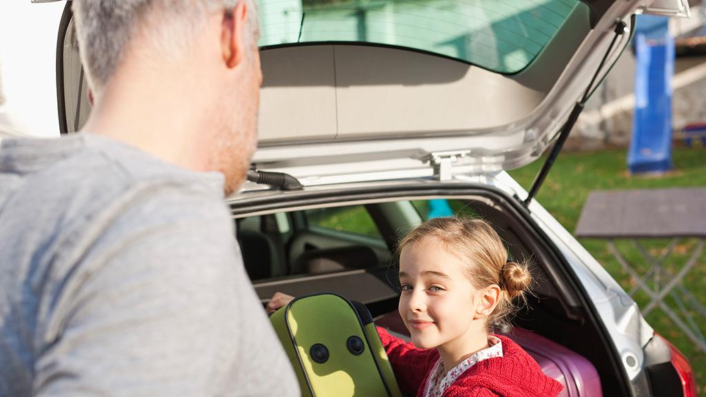 Vater und Tocher laden Koffer in Kofferraum von Auto