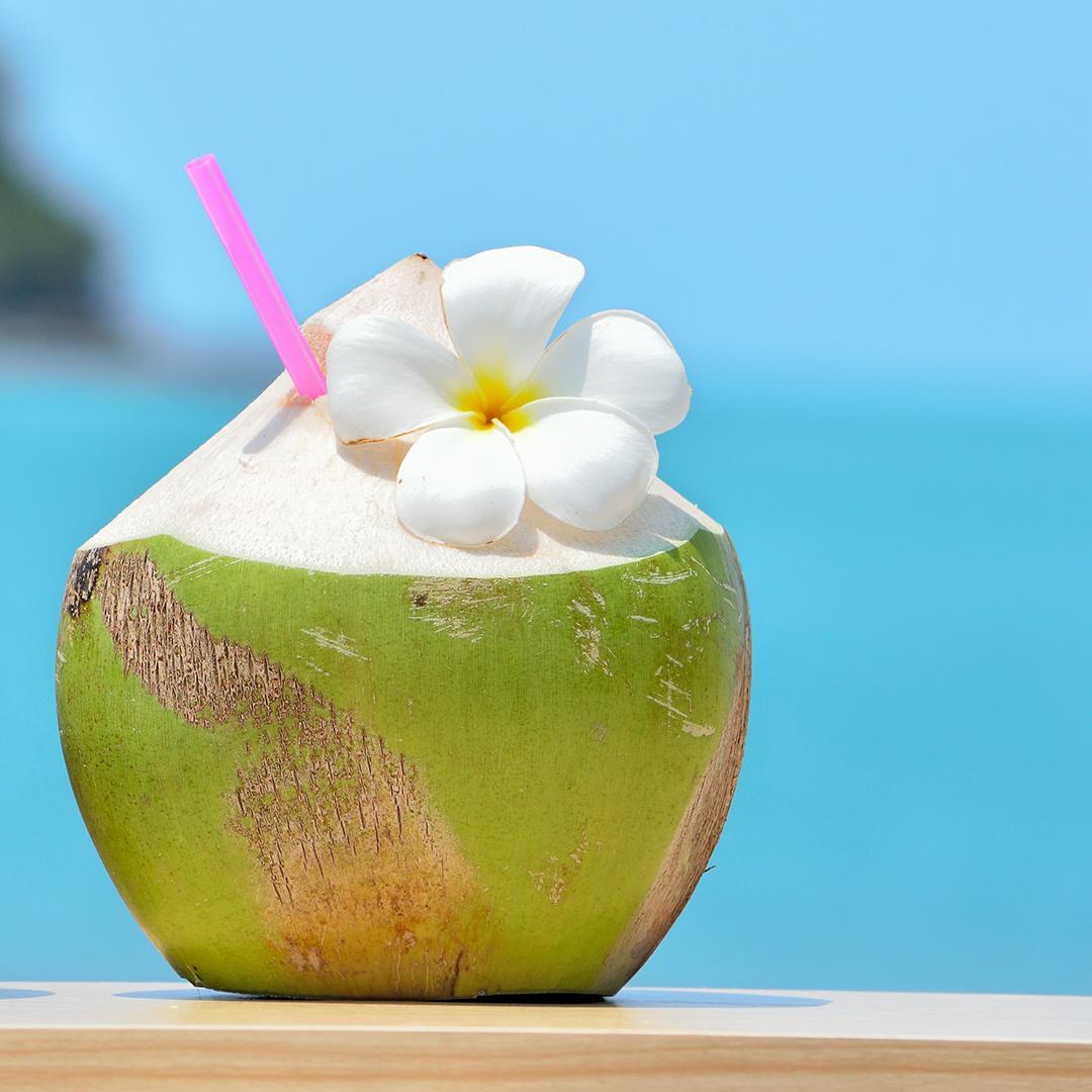 Kokosnuss mit Strohhalm und Blüte steht auf Tisch