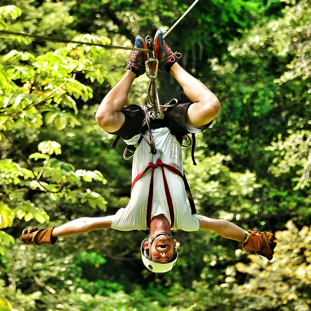 Man hängt kopfüber an Zipline und lacht