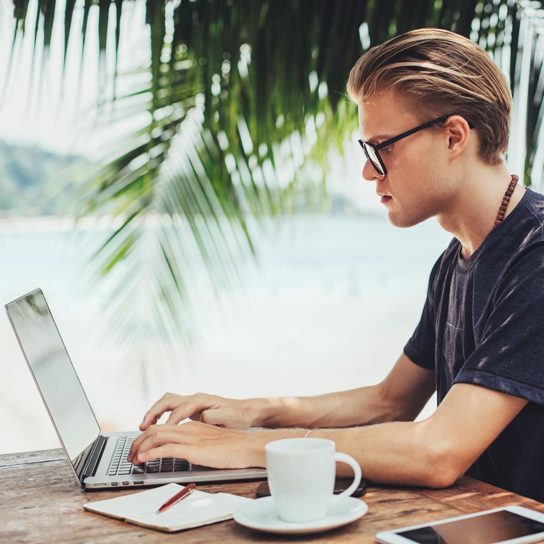 Mann sitzt vor Laptop mit Palmen im Hintergrund
