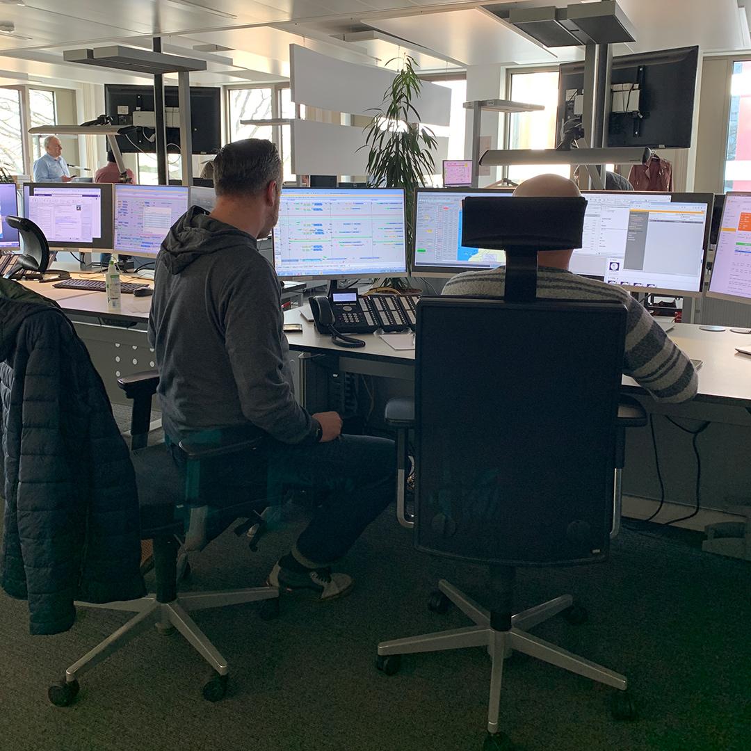 Zwei Condor Mitarbeiter sitzen an Schreibtisch im Central Control Center